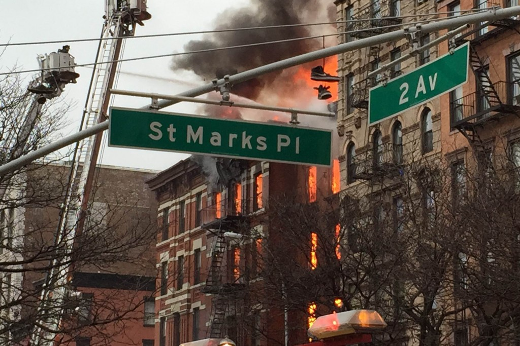 New York City firefighters work the scene of a large fire and a partial building collapse in the East Village neighborhood of New York on Thursday, March 26, 2015. Orange flames and black smoke are billowing from the facade and roof of the building near several New York University buildings.  (AP Photo/Suzanne Mitchell)