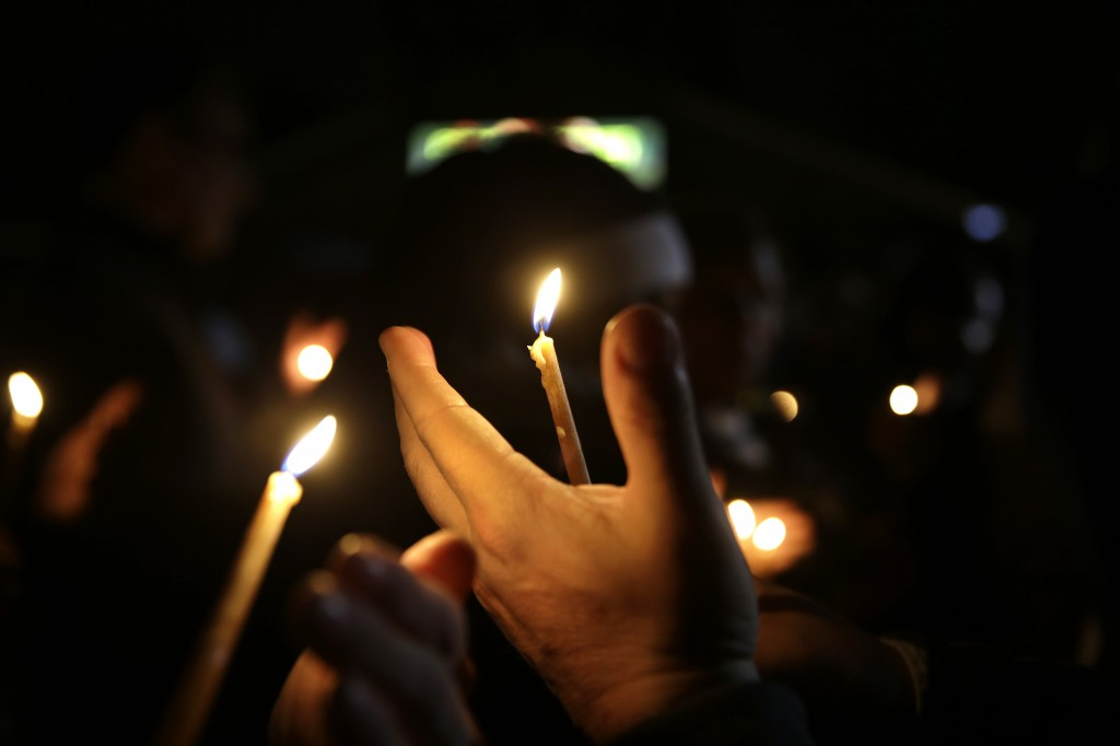 People take part in a candlelight vigil Thursday, March 12, 2015, in Ferguson, Mo. Two police officers were shot early Thursday morning in front of the Ferguson Police Department during a protest following the resignation of the city's police chief in the wake of a U.S. Justice Department report. (AP Photo/Jeff Roberson)