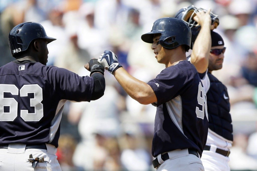 New York Yankees' Robert Refsnyder, center, is congratulated by Jose Pirela (63) after they both scored on Refsnyder's two-run home run during the first inning of a spring training exhibition baseball game against the Detroit Tigers in Lakeland, Fla., Friday, March 20, 2015. (AP Photo/Carlos Osorio)