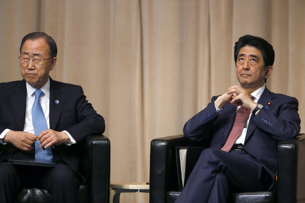 U.N. Secretary General Ban Ki-moon, left, and Japanese Prime Minister Shinzo Abe attend a symposium of the 70th anniversary of the United Nations at the UN University in Tokyo, Monday, March 16, 2015. (AP Photo/Shizuo Kambayashi)