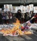 "A South Korean conservative activist burns a North Korean flag, portraits of North Korea leader Kim Jon Un and Kim Ki-jong, the suspect of slashing U.S. Ambassador to South Korea Mark Lippert, during a rally demanding speedy recovery of Lippert near the U.S. embassy in Seoul, South Korea, Friday, March 6, 2015. A knife attack Thursday that injured Lippert is the latest act of political violence in a deeply divided country where some protesters portray their causes as matters of life and death. The letters at a banner read "" A rally demanding speedy recovery of U.S. Ambassador to South Korea Mark Lippert  "" (AP Photo/Ahn Young-joon)"