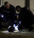 Police shine a light on a helmet as they investigate the scene where two police officers were shot outside the Ferguson Police Department Thursday, March 12, 2015, in Ferguson, Mo. (AP Photo/Jeff Roberson)