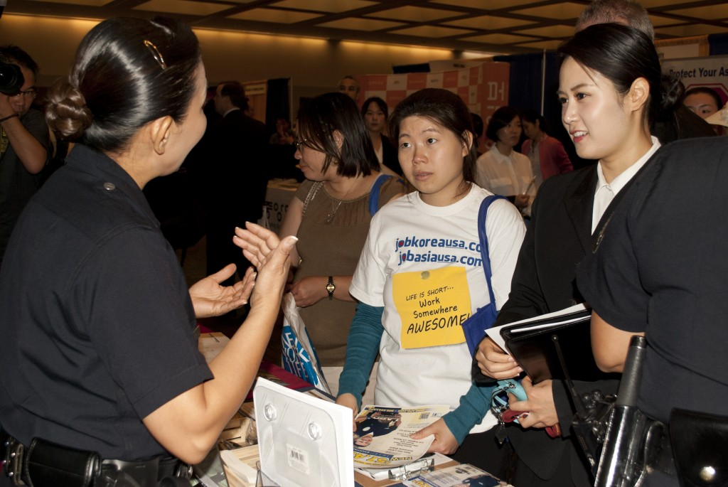 Officer Jin-ha Kim of the LAPD speaks with two women during the 2015 4th Hiring Fair. (Brian Han/Korea Times)