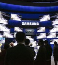 Attendees gather outside the Samsung booth, featuring its new SUHD TV, at the International CES Tuesday, Jan. 6, 2015, in Las Vegas. (AP Photo/Jae C. Hong)