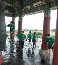 Student volunteers help clean the Korean Bell of Friendship in San Pedro, Calif., Saturday. (Kim Hyung-jae/Korea Times)