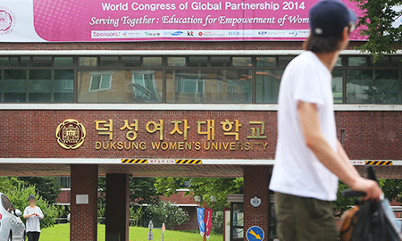 A man walks past the main gate of Duksung Women's University in Seoul in this Aug. 3, 2014, file photo. The university's president, Rhie Won-bok, recently said he wants to make the women-only school coeducational. (Yonhap)