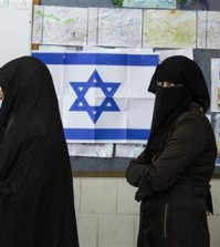 Bedouin women wait to cast their votes at a polling station in the town of Rahat, Tuesday, Mar. 17, 2015. Israelis are voting in early parliament elections following a campaign focused on economic issues such as the high cost of living, rather than fears of a nuclear Iran or the Israeli-Arab conflict. (AP Photo/Tsafrir Abayov)