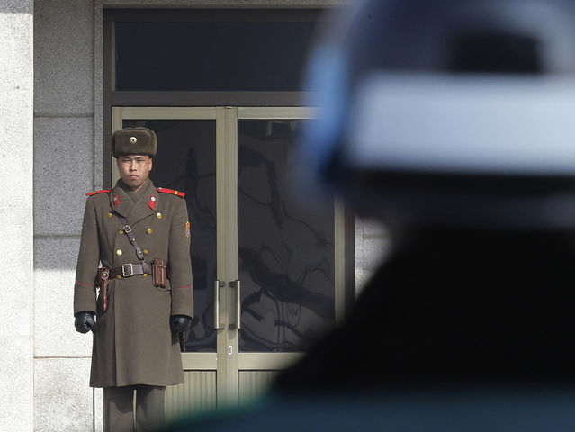 A North Korean army soldier, left, looks at the south side as a South Korean army soldier stands guard at the border village of Panmunjom, which has separated the two Koreas since the Korean War, South Korea Wednesday, Feb. 4, 2015. (AP Photo/Ahn Young-joon)