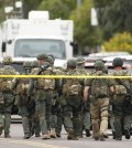 A SWAT team walks down the street near Adams Elementary School searching for a gunman on Wednesday, March 18, 2015 in Mesa, Ariz. A gunman wounded at least four people across multiple locations in the Phoenix suburb. The first shooting happened at a motel, and people were also wounded at a restaurant and nearby apartment complexes. (AP Photo/The Arizona Republic, Rob Schumacher)