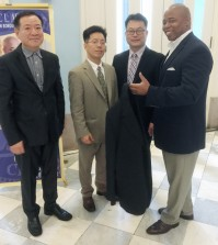 "Jung Young-hoon, former president of the Korean Dry Cleaners Association of New York, left, association Vice President Seo Jung-woo, center, and President Kim Sang-gyun, second from right, hand a ""Clothing of Love"" donation to Brooklyn Borough President Eric Adams, right, Monday."