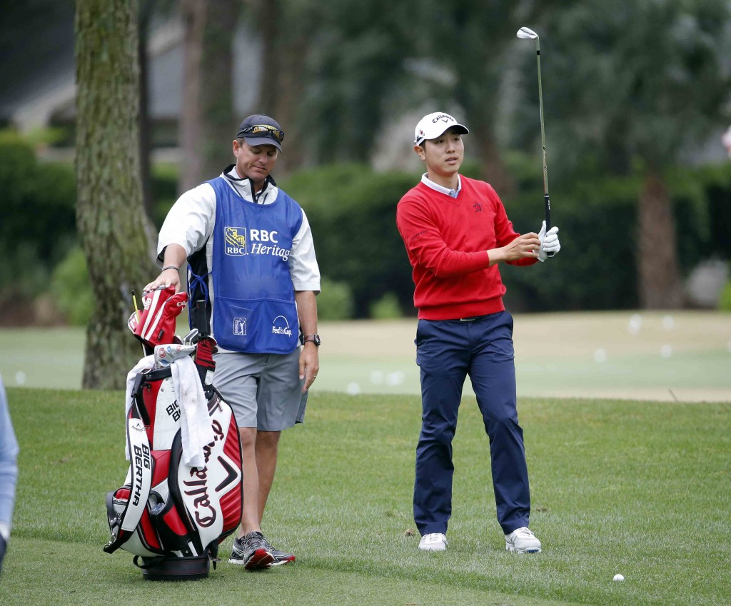 Sang-Moon Bae, right, of South Korea, prepares to hit on the ninth fairway during the first round of the RBC Heritage golf tournament in Hilton Head Island, S.C., Thursday, April 16, 2015. (AP Photo/Stephen B. Morton)