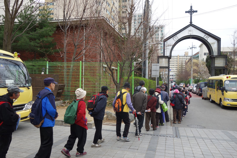 Koreans — many of them elderly — line up to receive 500 won, or about 50 cents, from Nam Seoul Church in southern Seoul. Each week, organizers say, 300 to 500 seniors show up at each church that offers the service, and the line starts hours in advance. (Photo credit: Elise Hu/NPR)