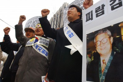"""Protesters with a portrait of South Korean Rev. Kim Dong-shik shout a slogan in a rally demanding release of Kim in front of the Foreign Ministry in Seoul Wednesday, Dec. 15, 2004. Kim, who was helping North Koreans living in hiding in China after fleeing their communist homeland, was kidnapped by a group of North Korean agents at Yanji in northern China in 2000. The letters on picket read """"Kidnapping Kim."""" (AP Photo/Ahn Young-joon)."""