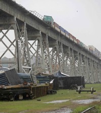 Train cars are crashed beneath the Huey P. Long Bridge, which crosses over the Mississippi River, after they toppled off the bridge from high winds in Jefferson Parish, La., just outside New Orleans, Monday, April 27, 2015. More than 200,000 homes and businesses lost power and at least four cars carrying freight containers were blown off the approach to the Huey P. Long Bridge outside New Orleans as a line of severe thunderstorms moved across southeast Louisiana. None of the freight containers held hazardous cargo, and nobody was injured,  (AP Photo/Gerald Herbert)