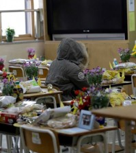 In this picture taken on Wednesday, April 8, 2015, an alumna sits in a victim's chair inside a classroom at Danwon High School in Ansan, south of Seoul, South Korea. One year ago the ferry Sewol carrying 325 second-year students on a field trip to a southern island sank; only 75 survived. Their classrooms in this city about an hour south of Seoul have barely changed from the day they left for the trip. (AP Photo/Lee Jin-man)