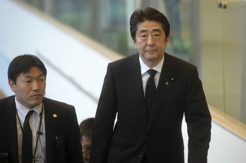Japan's Prime Minister Shinzo Abe, right, arrives at the state funeral for the late Lee Kuan Yew, at the University Cultural Center,  Sunday, March 29, 2015 in Singapore.  During a week of national mourning that began Monday after Lee's death at age 91, some 450,000 people queued for hours for a glimpse of Lee's coffin at Parliament House. A million people visited tribute sites at community centers across the island and leaders and dignitaries from more than two dozen countries attended the state funeral. (AP Photo/Joseph Nair)