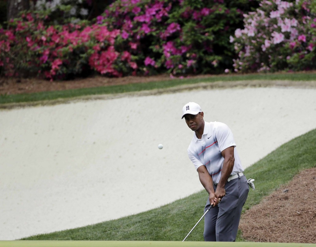 Tiger Woods chips to the 13th green during the first round of the Masters golf tournament Thursday, April 9, 2015, in Augusta, Ga. (AP Photo/David J. Phillip)