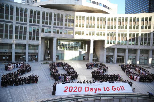 "In this Jan. 12, 2015 file photo, participants form human letters ""2020"" during a countdown event for the 2020 Tokyo Olympics in Tokyo. Organizers of the 2020 Tokyo Olympics promised the most innovative, impeccably run and ""sustainable"" Games ever. With just a little over five years to go, doubts are mounting that they might not deliver on that last pledge. On Tuesday, April 7, 2015, the World Wide Fund for Nature and others that are backing use of renewable energy, including Masato Mizuno, the sports-goods magnate who led Tokyo\'s bid for the games, issued a formal call for faster action. (AP Photo/Koji Sasahara, File)"