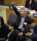 A North Korean defector, center, yells to try and drown out a statement being read by North Korean diplomats during a panel on North Korean human rights abuses, at United Nations headquarters, Thursday, April 30, 2015. (AP Photo/Seth Wenig)
