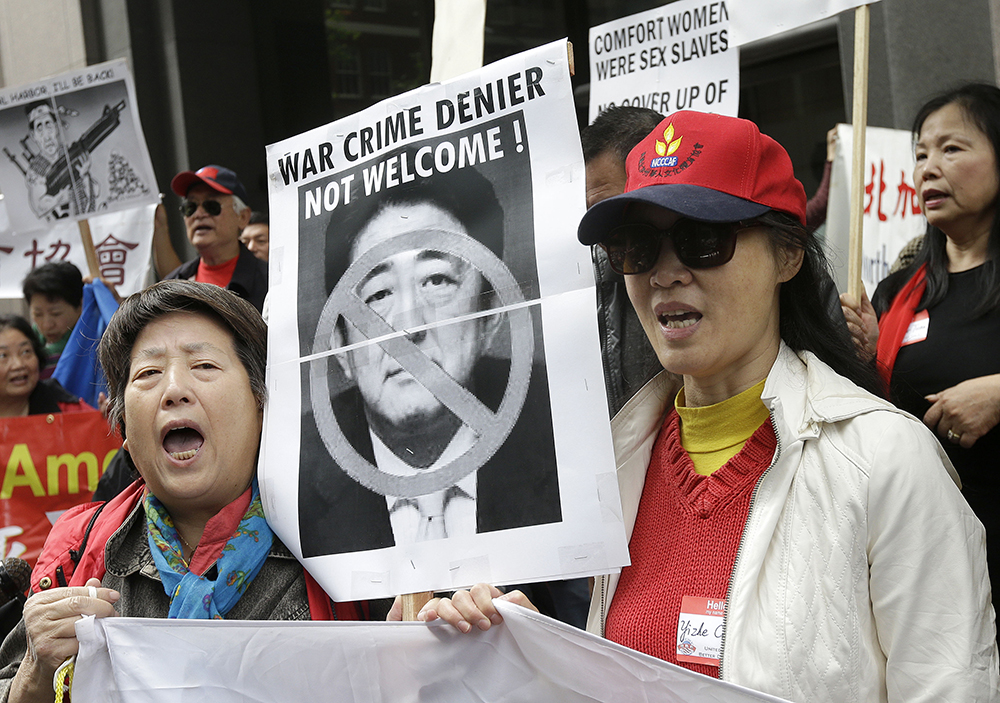 Lotus Gan, left, and Yize Chen yell with other Chinese American and Korean American protesters as they hold up a photo of Japanese Prime Minister Shinzo Abe during a rally outside of the Japanese Consulate in San Francisco, Tuesday, April 28, 2015. Hundreds of people protested outside the Japanese Consulate Tuesday, calling on Prime Minister Shinzo Abe to apologize for his country's atrocities toward other Asian countries during World War II. The protest came as Abe met with President Barack Obama in Washington, D.C., ahead of the prime minister's three-day visit to California this week. (AP Photo/Jeff Chiu)