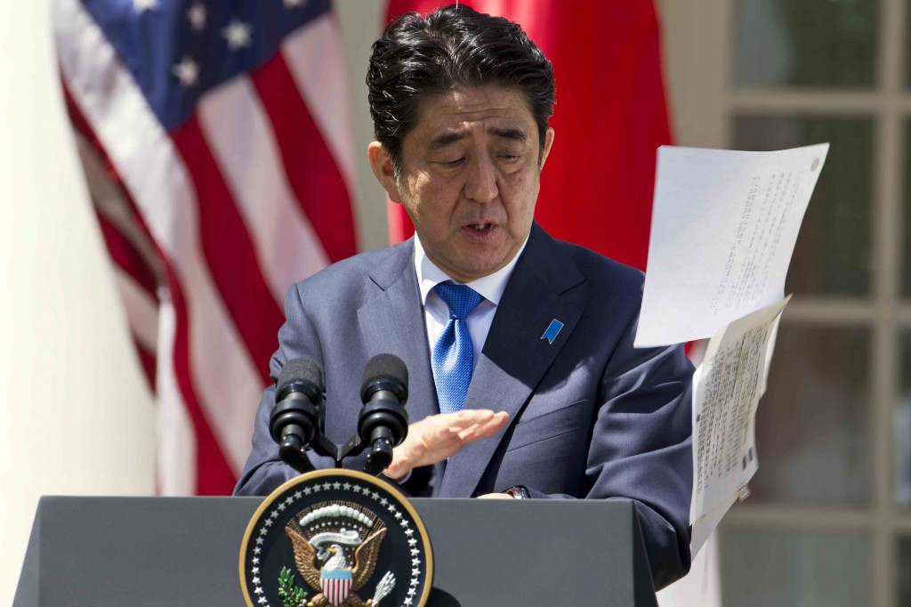 Japanese Prime Minister Shinzo Abe reacts as his papers are blown into the air in a gust of wind during his joint news conference with President Barack Obama, Tuesday, April 28, 2015, in the Rose Garden of the White House in Washington. (AP Photo/Jacquelyn Martin)