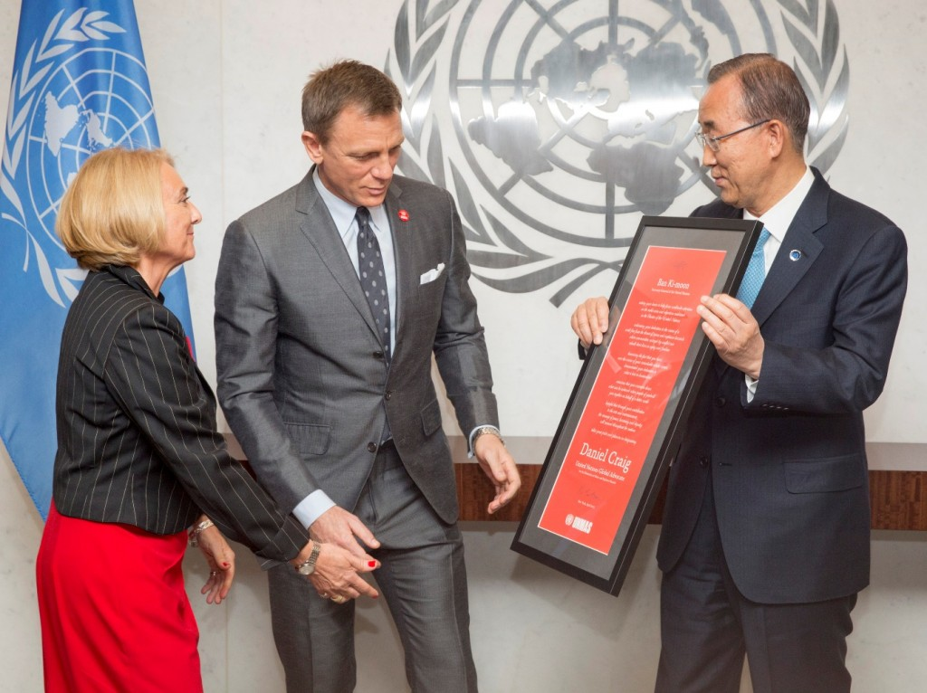 In this photo provided by the United Nations, U.N. Secretary General Ban Ki-moon, right, presents actor Daniel Craig, center, with a document designating him as the UN Global Advocate for the Elimination of Mines and Explosive Hazards, at United Nations headquarters, Tuesday, April 14, 2015. At left is Agnès Marcaillou, Director of the UN Mine Action Service. (Evan Schneider/The United Nations via AP)