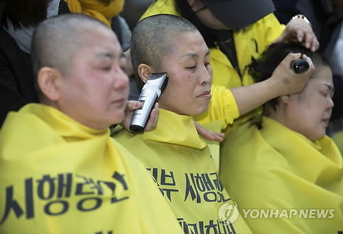 Family members of the victims of the April 2014 ferry disaster that claimed more than 300 lives have their heads shaved at Gwanghwamun Square in downtown Seoul on April 2, 2015, to demand the vessel's recovery and the truth behind the accident before the discussion of compensation measures for the families. (Yonhap)