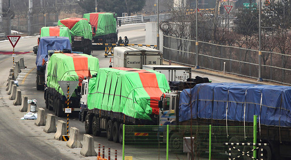 South Korean trucks loaded with sacks of flour for North Koreans left for the North Korean city of Kaesong on Friday. (Yonhap)