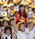 Students rejoice at Nguyen Viet Xuan Elementary School in Ho Chi Minh City on April 8, 2015, after receiving motorcycle helmets from South Korean retailer E-Mart. In Vietnam, many children are injured in motorcycle accidents as they do not wear helmets. E-Mart plans to give out 10,000 helmets a year. (pool photo) (Yonhap)