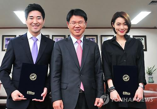 Woosuk University named Thailand taekwondo director Choi Young-seok, left, and K-pop star Kahi, right, as visiting professors of the school's taekwondo department Thursday. (Yonhap)