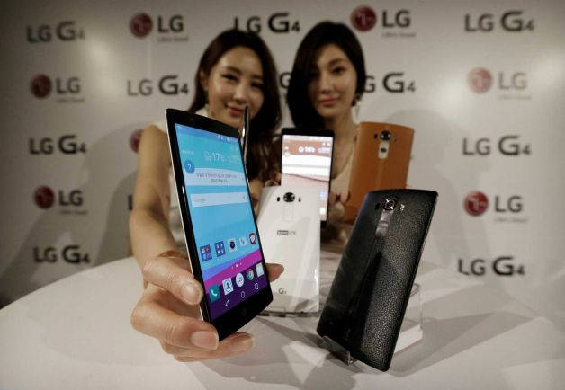 Models pose with LG Electronics' new G4 smartphones during its unveiling ceremony in Seoul, South Korea Wednesday, April 29, 2015. LG Electronics Inc. says its quarterly profit plunged 59 percent from a year earlier as losses from TVs offset a modest improvement in its smartphone business. (AP Photo/Ahn Young-joon)