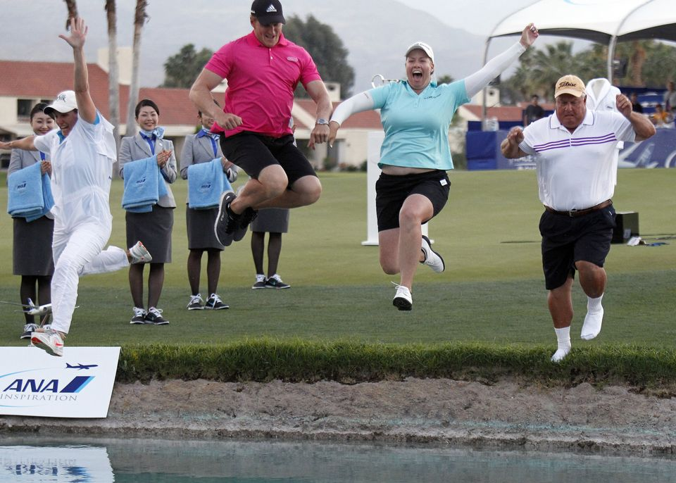 Brittany Lincicome, second from right, leaps into Poppy's Pond with her father, Tom Lincicome, right, her fiancé, Dewald Gouws and her caddie, Missy Pederson, left, after winning an LPGA Tour golf tournament at Mission Hills Country Club, Sunday, April 5, 2015, in Rancho Mirage, Calif. (AP Photo/Alex Gallardo)