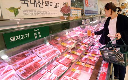 A shopper takes a look at pork at a retailer. (Korea Times file)