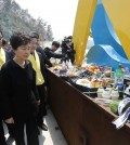 South Korean President Park Geun-hye, front right, looks at foods and beverages dedicated for the victims of the sunken ferry Sewol as she arrives to offer her condolences to the bereaved relatives of the victims at a port in Jindo, South Korea, Thursday, April 16, 2015. Tears and grief mixed with raw anger Thursday as black-clad relatives mourned the 300 people, mostly high school kids, killed one year ago when the ferry Sewol sank in cold waters off the southwestern South Korean coast. (Lee Jeong-ryong/Yonhap via AP) KOREA OUT
