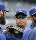 Los Angeles Dodgers starting pitcher Hyun-Jin Ryu, center, gets a ball from Los Angeles Dodgers' Scott Van Slyke, left, during warmups prior to a baseball game against the San Diego Padres, Saturday, April 25, 2015, in San Diego. (AP Photo/Lenny Ignelzi))