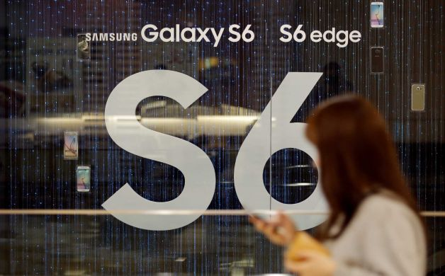 A woman walks by the advertisement of Samsung's Galaxy S6 smartphone outside its showroom in Seoul, South Korea, Wednesday, April 29, 2015. Samsung Electronics Co. said its first-quarter net income plunged 39 percent as consumers switched to bigger iPhones, squeezing its profit from the mobile business to less than half from a year earlier. (AP Photo/Lee Jin-man)