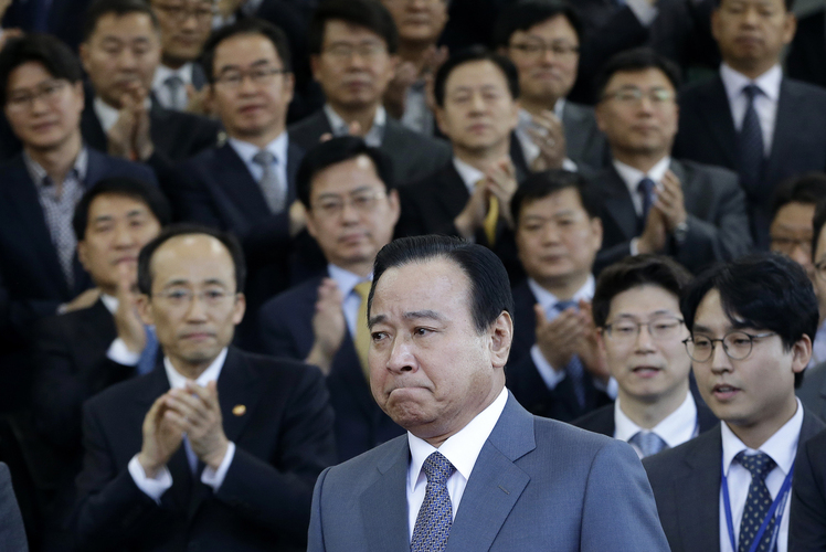 South Korean Prime Minister Lee Wan Koo, bottom center, leaves the Central Government Complex after his farewell ceremony in Seoul, South Korea Monday, April 27, 2015. South Korean President Park Geun-hye on Monday accepted the resignation offer by her prime minister over a bribery scandal. (AP Photo/Ahn Young-joon)
