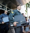 "Federal agents load a van with boxes and computers taken from the headquarters of the Confederation of North, Central America and Caribbean Association Football (CONCACAF,) Wednesday, May 27, 2015, in Miami Beach, Fla. Swiss prosecutors opened criminal proceedings into FIFA's awarding of the 2018 and 2022 World Cups, only hours after seven soccer officials were arrested Wednesday pending extradition to the U.S. in a separate probe of ""rampant, systemic, and deep-rooted"" corruption. (AP Photo/Wilfredo Lee)"