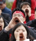 "Union members of Korea Exchange Bank shout slogans during a rally in front of Financial Services Commission in Seoul, South Korea, Friday, Nov. 18, 2011. The Korean read ""Defend, Foreign Exchange Bank."" (AP Photo/Lee Jin-man)"