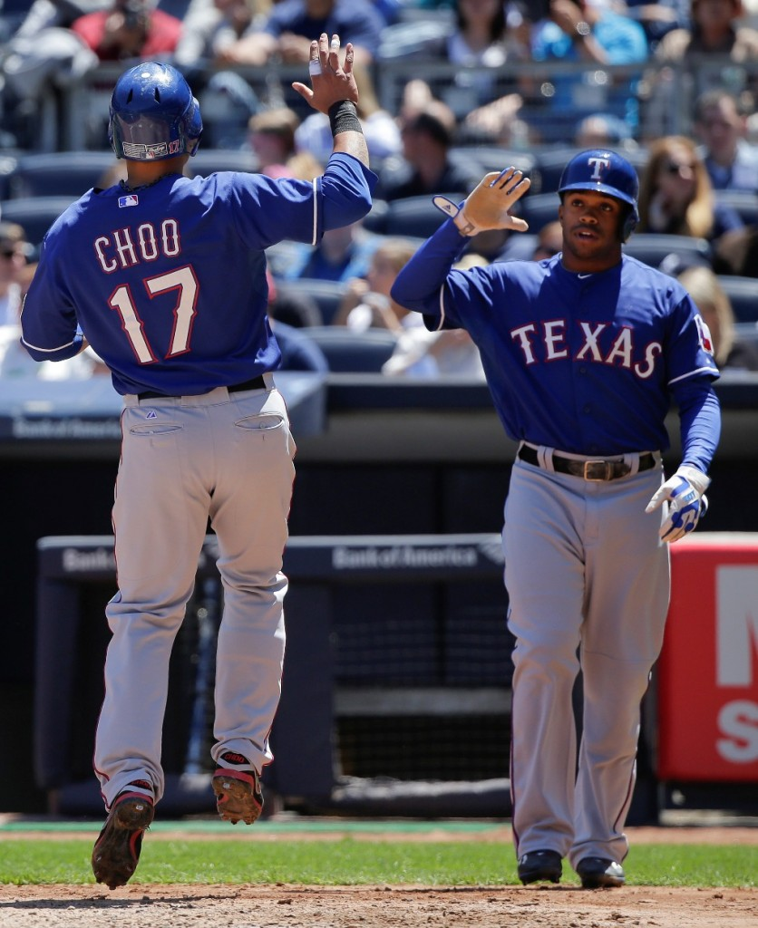 Texas Rangers' Shin-Soo Choo (17) is greeted by Delino DeShields (7) after both scored on a base hit by Rangers designated hitter Prince Fielder during the third inning of a baseball game against the New York Yankees, Saturday, May 23, 2015, in New York. (AP Photo/Julie Jacobson)
