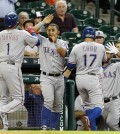 Texas Rangers'  Shin-Soo Choo (17) and Elvis Andrus (1) are congratulated as they score in the first inning on a double by Prince Fielder in a baseball game Tuesday May 5, 2015 in Houston. (AP Photo/Bob Levey)