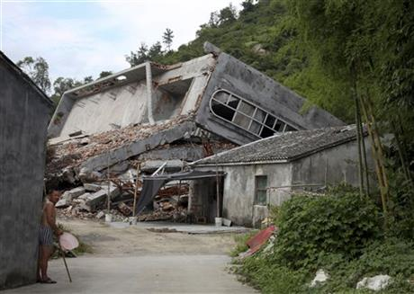 FILE - In this file photo taken July 16, 2014, a man stands near the razed remains of a Catholic church in a village in Pingyang county of Wenzhou in eastern China's Zhejiang province. The Chinese province where authorities have forcibly removed hundreds of rooftop crosses from Protestant and Catholic churches has proposed a ban on any further placement of the religious symbol atop sanctuaries. (AP Photo/Didi Tang, File)