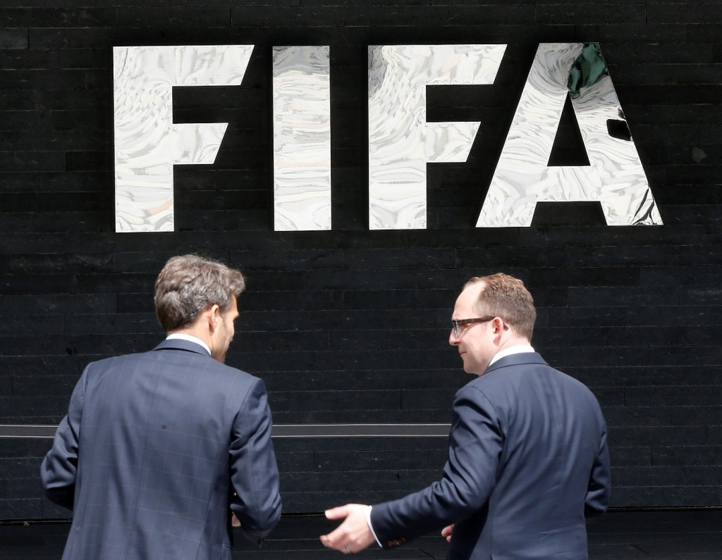 "Two men talk to each other in front of the FIFA logo at the FIFA headquarters in Zurich, Switzerland, Wednesday, May 27, 2015. Swiss prosecutors opened criminal proceedings into FIFA's awarding of the 2018 and 2022 World Cups, only hours after seven soccer officials were arrested Wednesday pending extradition to the U.S. in a separate probe of ""rampant, systemic, and deep-rooted"" corruption. (AP Photo/Michael Probst)"