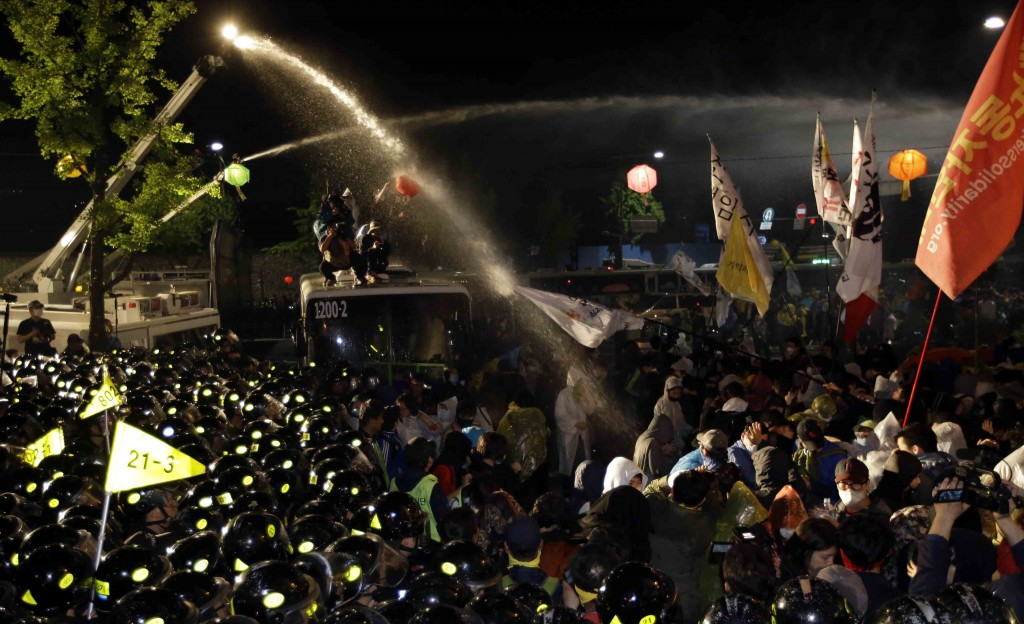 South Korean police officers spray water to disperse protesters as protesters try to march to the presidential house during a rally against government's policy about the sunken ferry Sewol in Seoul, South Korea, Friday, May 1, 2015. Thousands of South Koreans marched in Seoul on Friday for a third week to protest government labor policies and the handling of a ferry disaster that killed more than 300 people a year ago. (AP Photo/Lee Jin-man)
