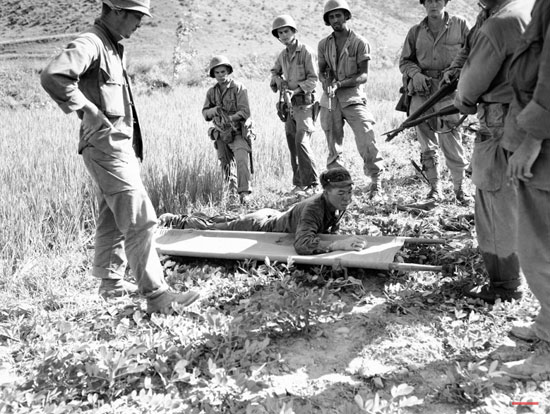 U.S. Marines cover wounded North Korean soldier as he hoists himself to stretcher in the Naktong River sector of the Korean front on August 23, 1950. The captive was flushed out of a nearby rice paddy, still clutching his automatic weapons. A search of his clothing disclosed an American watch, lighter and other items apparently taken from a dead U.S. soldier. (AP Photo/Max Desfor)