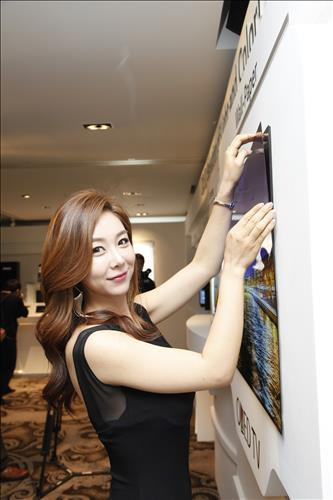 A model gently lifts the ultra-slim, detachable wallpaper OLED panel made by LG Display Co. at a media event held in Seoul on May 19, 2015. (Photo courtesy of LG Display Co.)