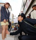 "Actors re-enact the police crackdown on miniskirts in the 1970s during the Chungjang Recollection Festival in Gwangju, Wednesday. In those days, officers used rulers to measure women's skirts to make sure they were not ""too short,"" but one restaurant in China is measuring them for a different reason. (Yonhap)"