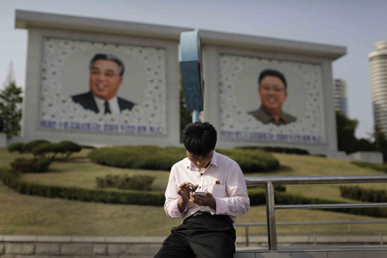 In this Tuesday, May 5, 2015, photo, a man sits in front of portraits of the late North Korean leaders Kim Il Sung, left, and Kim Jong Il, right, as he uses his smartphone in Pyongyang, North Korea. North Korean officials have unveiled a mobile-friendly online shopping site. (AP Photo/Wong Maye-E)