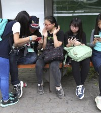South Korean middle school students use their smartphones at a bus station in Seoul, South Korea, Friday, May 15, 2015. (AP Photo/Ahn Young-joon)