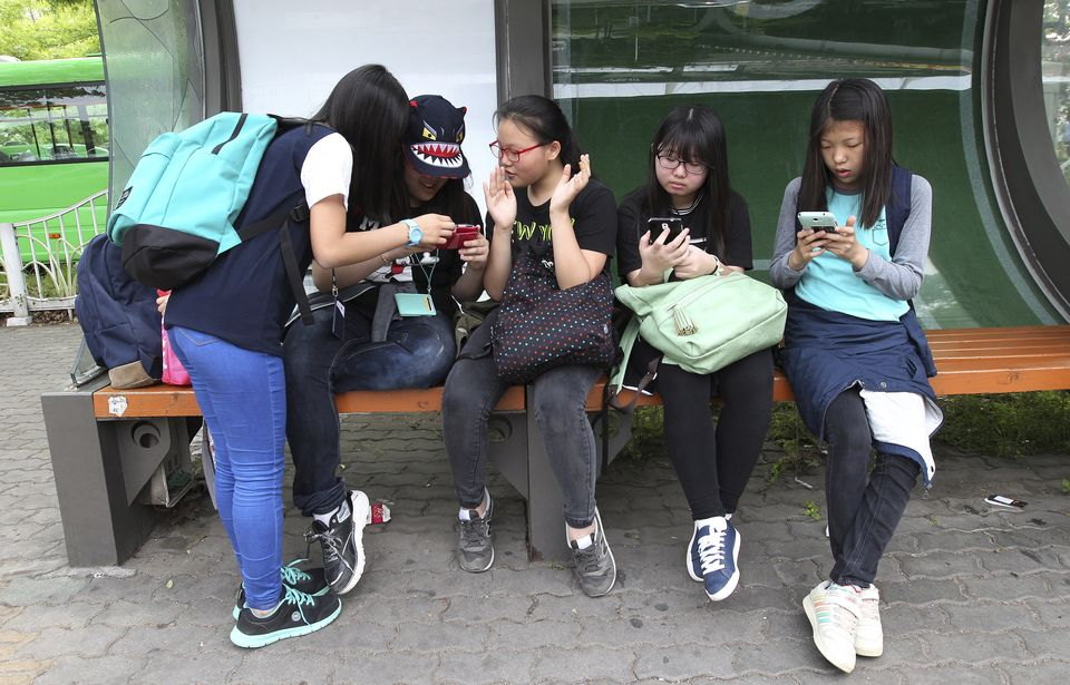 "South Korean middle school students use their smartphones at a bus station in Seoul, South Korea, Friday, May 15, 2015. The app, ""Smart Sheriff,"" was funded by the South Korean government primarily to block access to pornography and other offensive content online. But its features go well beyond that. Smart Sheriff and at least 14 other apps allow parents to monitor how long their kids use their smartphones, how many times they use apps and which websites they visit. Some send a child's location data to parents and issue an alert when a child searches keywords such as ""suicide,"" ''pregnancy"" and ""bully"" or receives messages with those words. (AP Photo/Ahn Young-joon)"